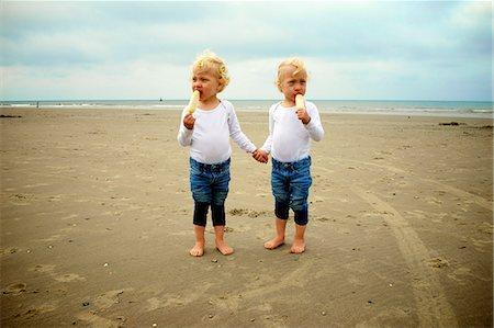 Twins eating icecream on the beach Stock Photo - Premium Royalty-Free, Code: 6106-08181512