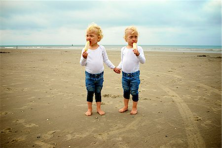 Twins eating icecream on the beach Stock Photo - Premium Royalty-Free, Code: 6106-08181512