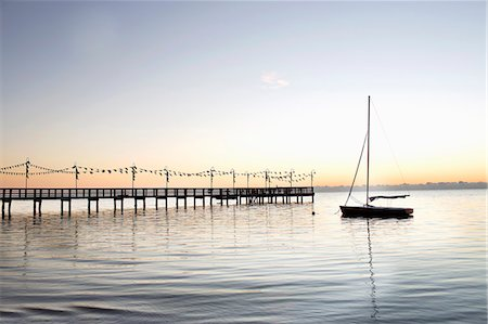 sailboat  ocean - Wooden jetty with flags stretching out into Bay Stock Photo - Premium Royalty-Free, Code: 6106-08100282