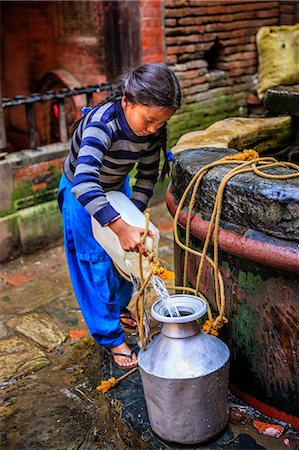 Young Nepali girl getting water from a well Stock Photo - Premium Royalty-Free, Code: 6106-08100374