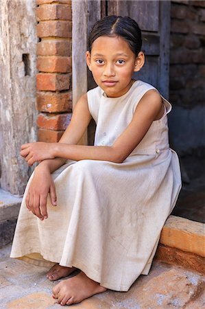 Young Nepali girl sitting outside her house Stock Photo - Premium Royalty-Free, Code: 6106-08277793