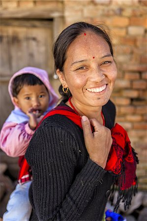 Young Nepali woman carrying her baby Stock Photo - Premium Royalty-Free, Code: 6106-08277848