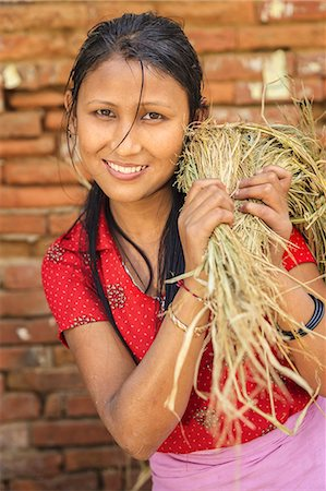 Nepali woman carrying a straw in Bhaktapur Stock Photo - Premium Royalty-Free, Code: 6106-08277807