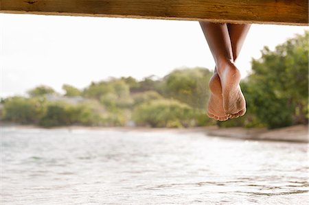 Woman's feet dangle from wooden platform. Stock Photo - Premium Royalty-Free, Code: 6106-08211165
