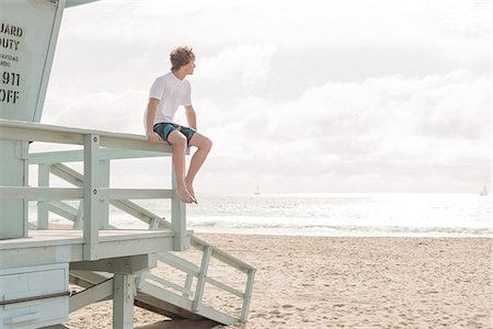 Teen boy sits on lifeguard platform, looks out Stock Photo - Premium Royalty-Free, Code: 6106-08211177