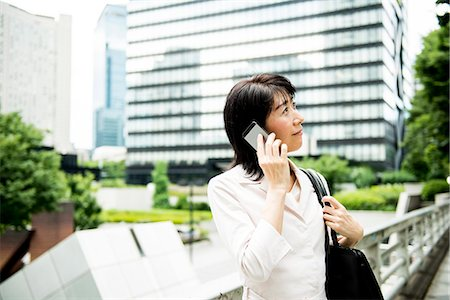 Business woman talking on mobile phone Stock Photo - Premium Royalty-Free, Code: 6106-08480517