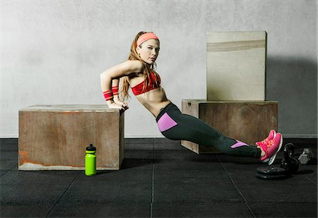 female - Athlete doing dips for triceps in a crossfit gym Stock Photo - Premium Royalty-Free, Code: 6106-08509166