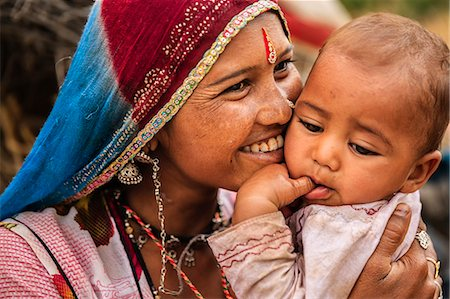 Young Indian mother holding her little baby Stock Photo - Premium Royalty-Free, Code: 6106-08527546