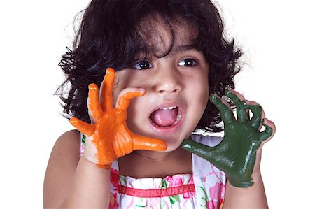 Close-up of a young girl with colored palms Stock Photo - Premium Royalty-Free, Code: 6107-06117577