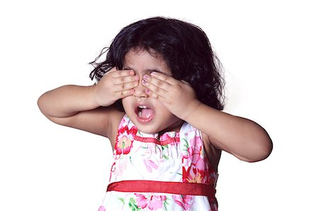 Portrait of a young girl covering her eyes with her hands Stock Photo - Premium Royalty-Free, Code: 6107-06117584
