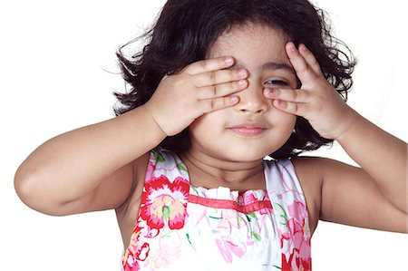 Portrait of a young girl covering her eyes with her hands Stock Photo - Premium Royalty-Free, Code: 6107-06117585