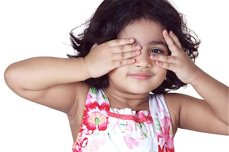Portrait of a young girl covering her eyes with her hands Stock Photo - Premium Royalty-Free, Code: 6107-06117586