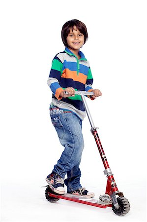 Portrait of little boy with foot push skate cycle Stock Photo - Premium Royalty-Free, Code: 6107-06117701