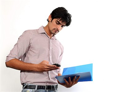 east indian (male) - Portrait of man holding file and texting on mobile Stock Photo - Premium Royalty-Free, Code: 6107-06117936