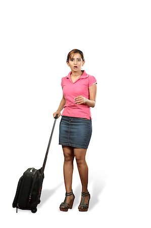 Portrait of young woman with rolling suitcase Stock Photo - Premium Royalty-Free, Code: 6107-06118101