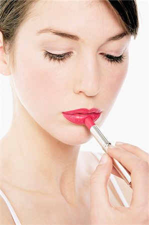 Young Woman face making-up with a lipstick, close-up (studio) Stock Photo - Premium Royalty-Free, Code: 6108-05855620