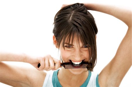 Portrait of a young woman holding a comb in her mouth Stock Photo - Premium Royalty-Free, Code: 6108-05855841
