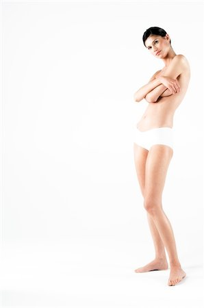 Naked woman in panties, hands on her breasts (studio) Stock Photo - Premium Royalty-Free, Code: 6108-05855849