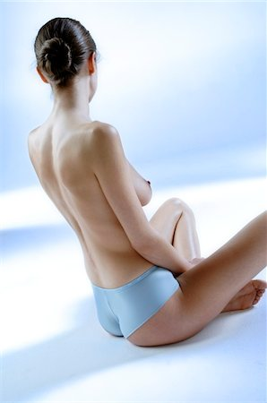 Naked woman in panties, sitting, view from the back (studio) Stock Photo - Premium Royalty-Free, Code: 6108-05855856