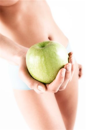 Naked woman in panties, holding a green apple, close up (studio) Stock Photo - Premium Royalty-Free, Code: 6108-05855861