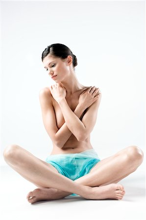 sit - Naked woman in panties, sitting down cross-legged, arms on her breasts (studio) Stock Photo - Premium Royalty-Free, Code: 6108-05855870
