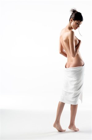 Naked woman view from the back, bath towel on her buttocks (studio) Stock Photo - Premium Royalty-Free, Code: 6108-05855879