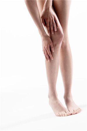 Woman legs, hands on thigh and knee, close up (studio) Stock Photo - Premium Royalty-Free, Code: 6108-05855897