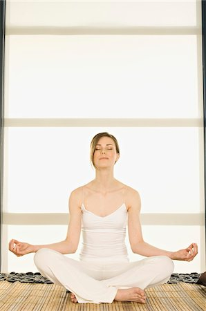 Young woman sitting cross-legged, yoga attitude, shut eyes Stock Photo - Premium Royalty-Free, Code: 6108-05855946