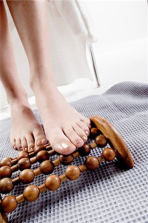 Young woman using wooden massager on her naked feet Stock Photo - Premium Royalty-Free, Code: 6108-05855905