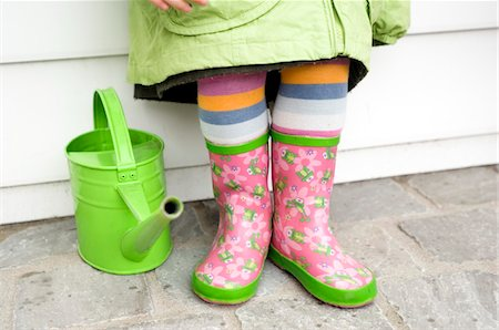 season - Little girl in boots, close-up, green watering can Stock Photo - Premium Royalty-Free, Code: 6108-05856064
