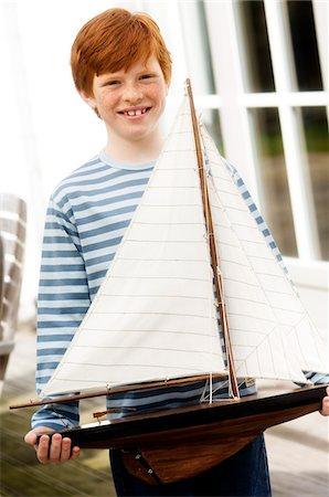 Boy holding a model boat Stock Photo - Premium Royalty-Free, Code: 6108-05856079