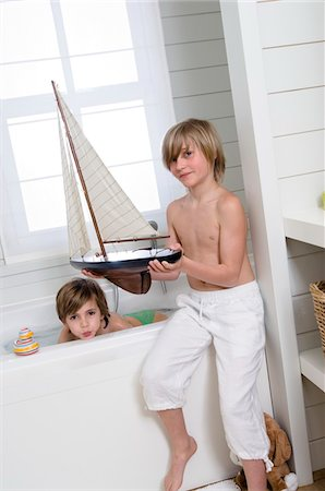 2 boys in bathroom, one having a bath, the other holding a model boat Stock Photo - Premium Royalty-Free, Code: 6108-05856099