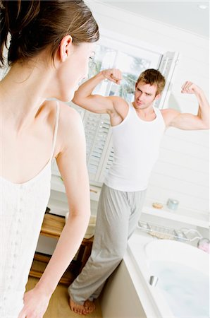 Couple in bathroom, woman watching man flexing muscles Stock Photo - Premium Royalty-Free, Code: 6108-05856142