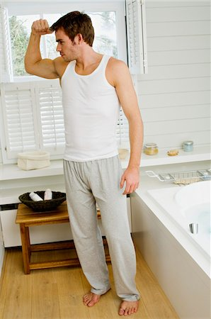 Young man flexing muscles in bathroom Stock Photo - Premium Royalty-Free, Code: 6108-05856154