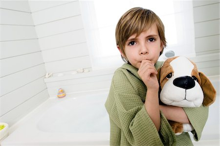 Little boy sucking his thumb, holding stuffed dog Stock Photo - Premium Royalty-Free, Code: 6108-05856101