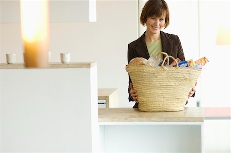 supply - Young smiling woman with shopping basket in the kitchen Stock Photo - Premium Royalty-Free, Code: 6108-05856317