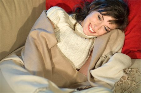 sweater - Young woman lying on a sofa, smiling, wrapped in blanket Stock Photo - Premium Royalty-Free, Code: 6108-05856449