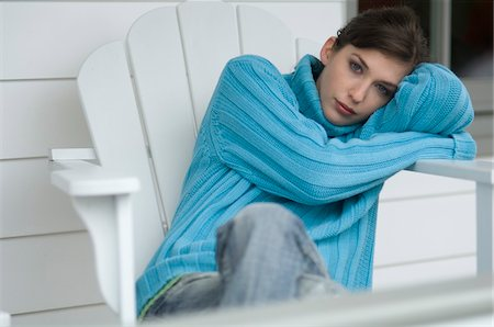 sweater - Young woman sitting on a chair, looking at the camera, outdoors Stock Photo - Premium Royalty-Free, Code: 6108-05856479