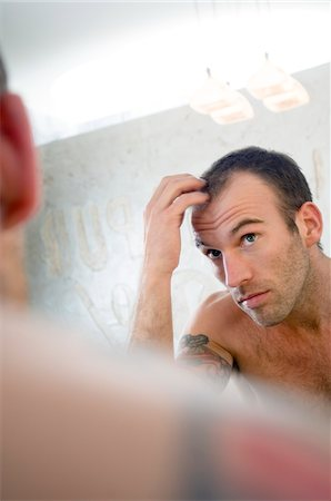 Tattooed man, barechested, looking in bathroom mirror Stock Photo - Premium Royalty-Free, Code: 6108-05856548