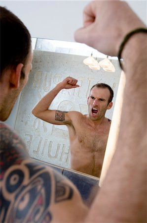 superior - Tattooed man flexing muscles in front of bathroom mirror Stock Photo - Premium Royalty-Free, Code: 6108-05856519