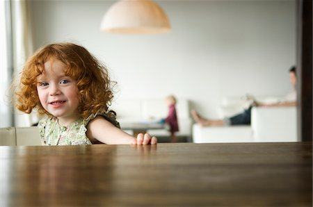 Little girl looking at the camera, coffee table in the foreground Stock Photo - Premium Royalty-Free, Code: 6108-05856661