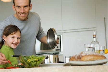 Man and little girl cooking, smiling for the camera Stock Photo - Premium Royalty-Free, Code: 6108-05856678