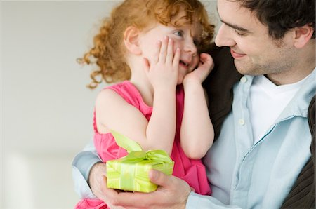 Man giving present to little girl Stock Photo - Premium Royalty-Free, Code: 6108-05856691