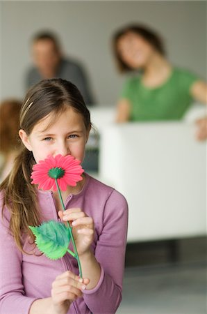 smelly - Little girl holding a plastic flower in front of her face, couple in the background Stock Photo - Premium Royalty-Free, Code: 6108-05856627