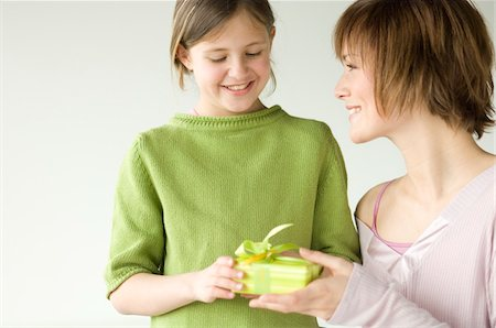 Woman giving a present to little girl Stock Photo - Premium Royalty-Free, Code: 6108-05856636