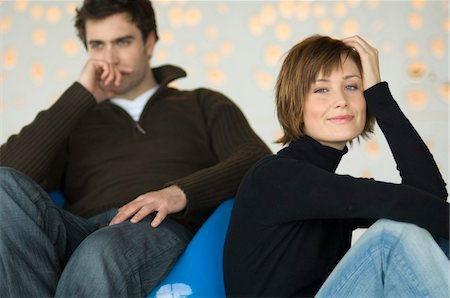 superior - Couple sitting in living-room, woman looking at the camera, man thinking in the background Stock Photo - Premium Royalty-Free, Code: 6108-05856711