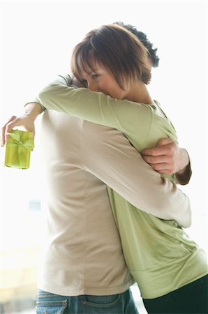 Couple embracing, woman holding present Stock Photo - Premium Royalty-Free, Code: 6108-05856714