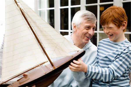 Senior man and boy holding a model boat, outdoors Stock Photo - Premium Royalty-Free, Code: 6108-05856858