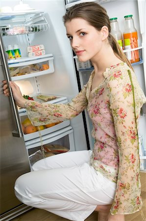 fridge - Woman crouching in front of refrigerator Stock Photo - Premium Royalty-Free, Code: 6108-05856940