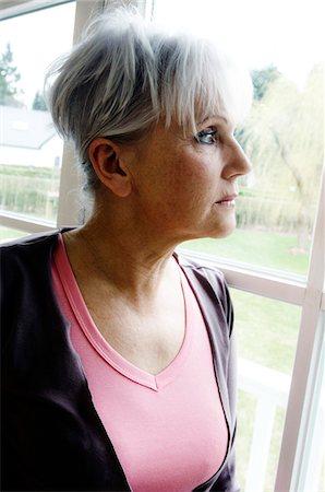 dead woman - Thinking senior woman looking through a window Stock Photo - Premium Royalty-Free, Code: 6108-05856901